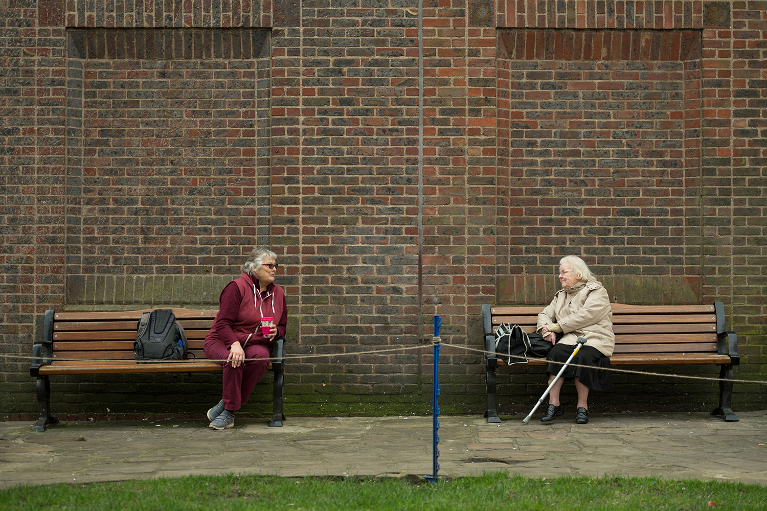 Two women observe social distancing measures amid the coronavirus outbreak as they speak to each other from adjacent park benches in York, northern England, on March 19. OLI SCARFF/AFP via Getty Images