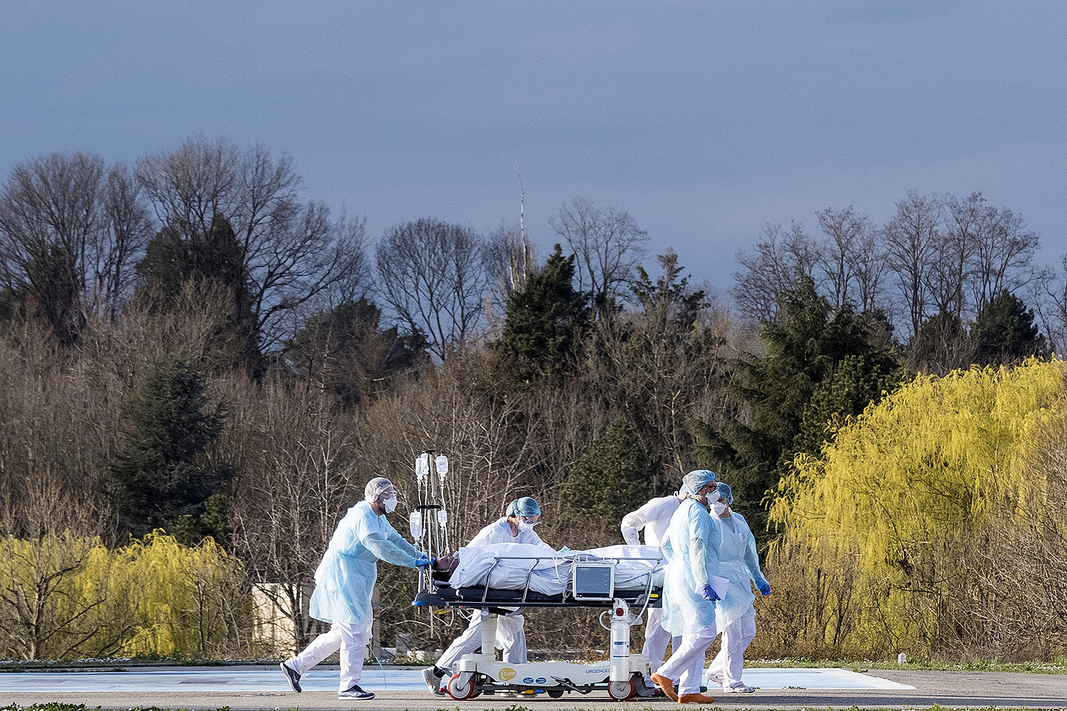 Medical staff push a patient on a gurney to a waiting helicopter at the Emile Muller hospital in Mulhouse, eastern France, on March 17. The patient was being evacuated to another hospital as the coronavirus spread. SEBASTIEN BOZON/AFP via Getty Images