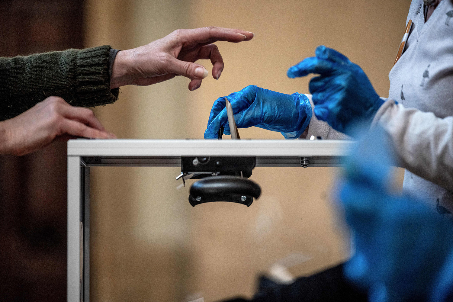 A voter casts their ballot at a polling station in Lyon, France, on March 15 during the first round of mayoral elections. With fears of coronavirus high, the country postponed the second round of local elections until June. JEFF PACHOUD/AFP via Getty Images