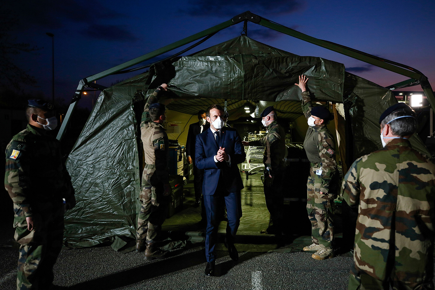 French President Emmanuel Macron exits a military field hospital outside Emile Muller Hospital in Mulhouse, France, on March 25. MATHIEU CUGNOT/POOL/AFP via Getty Images