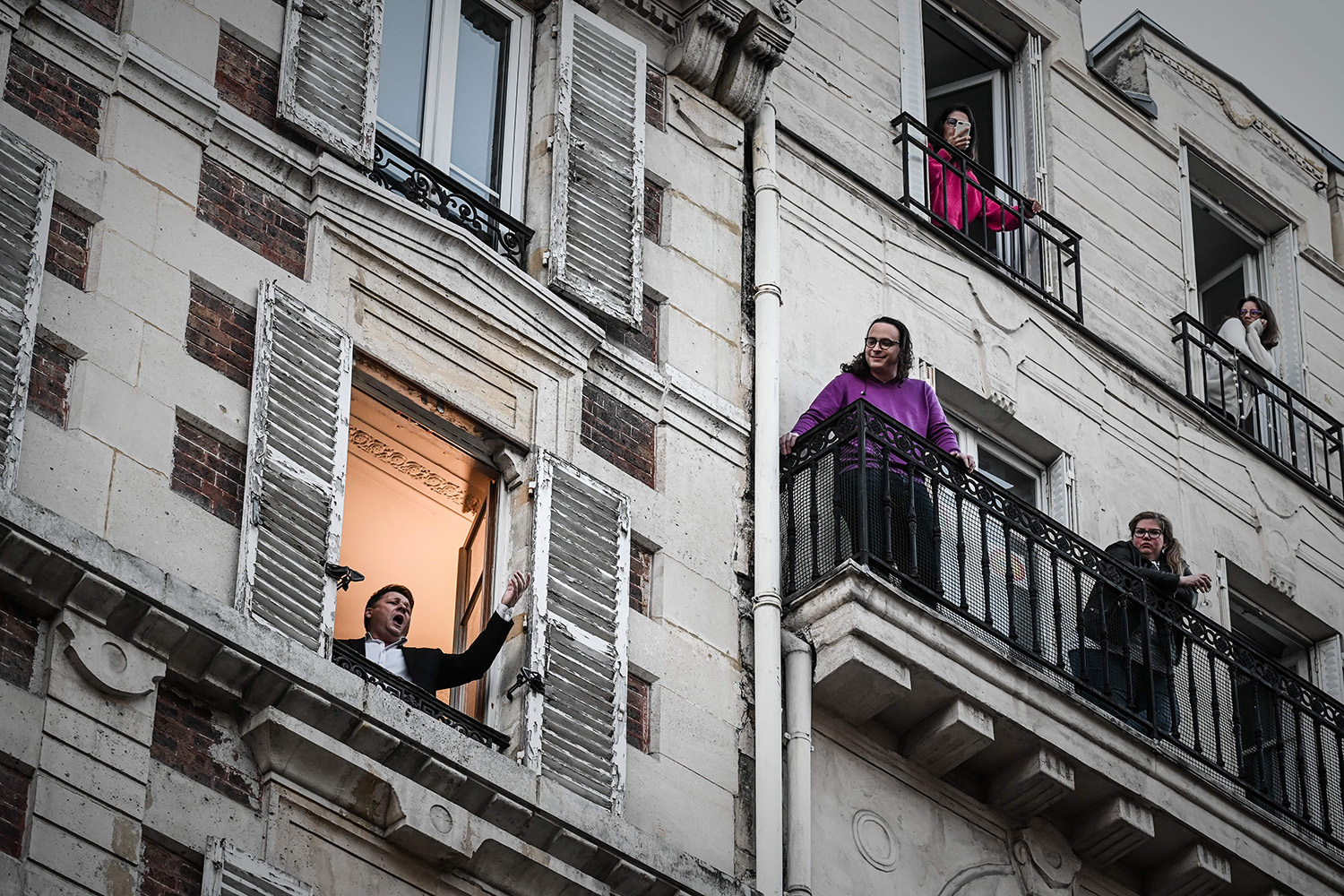 "French opera singer Stéphane Sénéchal performs the song ""O Sole Mio"" from his window in Paris on March 26. PHILIPPE LOPEZ/AFP via Getty Images"