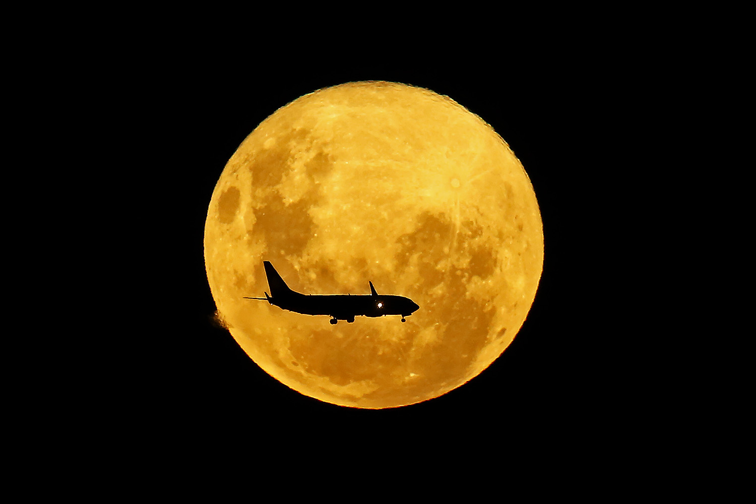 A plane passes in front of the full moon as seen from Curitiba, Brazil, on March 9. HEULER ANDREY/AFP via Getty Images
