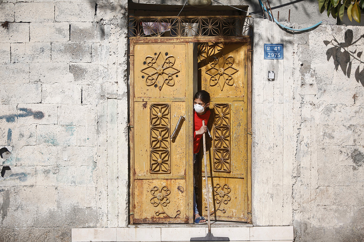 A girl wearing a protective mask sweeps outside her home in Gaza City on March 22.