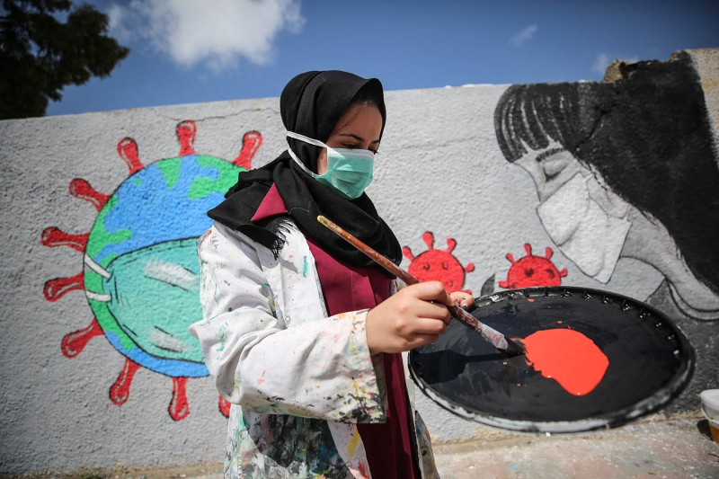 Palestinian painters work on a mural to draw attention to the novel coronavirus pandemic in Khan Yunis, Gaza, on March 28.