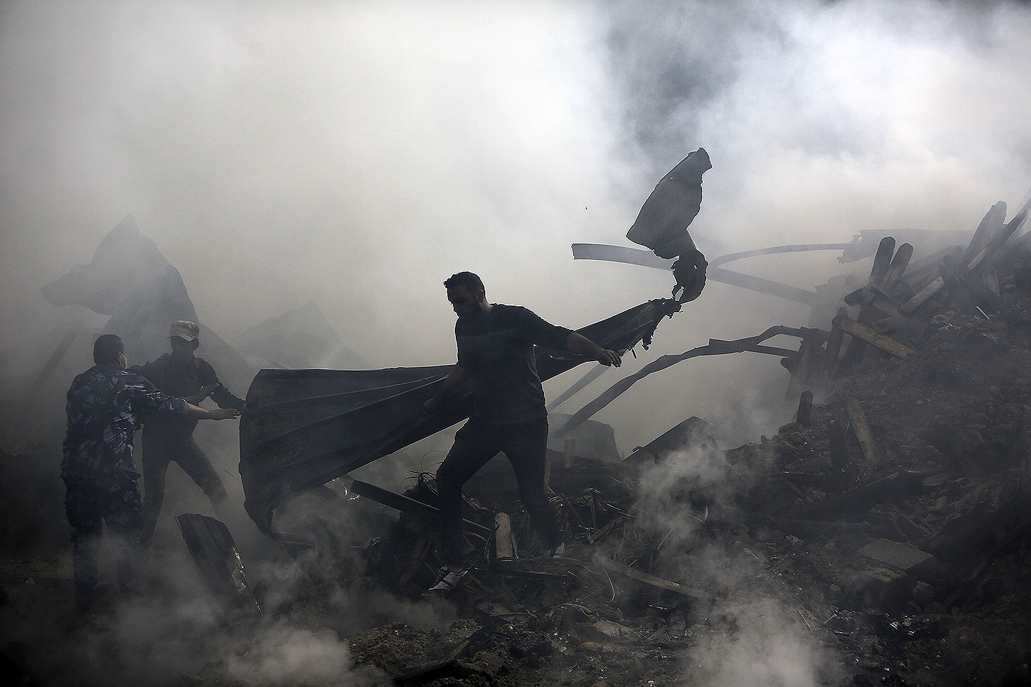 Palestinians put out a fire that broke out in a market in the refugee camp of Nuseirat in central Gaza Strip on March 5. MOHAMMED ABED/AFP via Getty Images