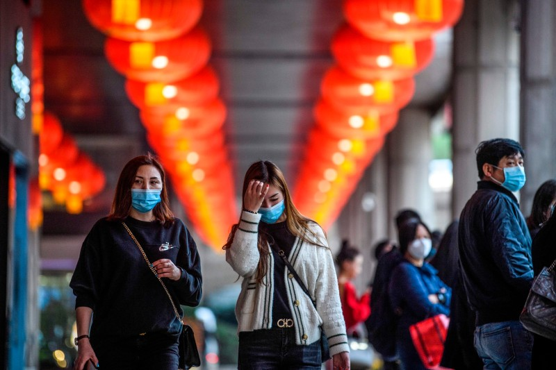 Pedestrians wear face masks as they walk outside the New Orient Landmark hotel in Macau on Jan. 22, 2020.