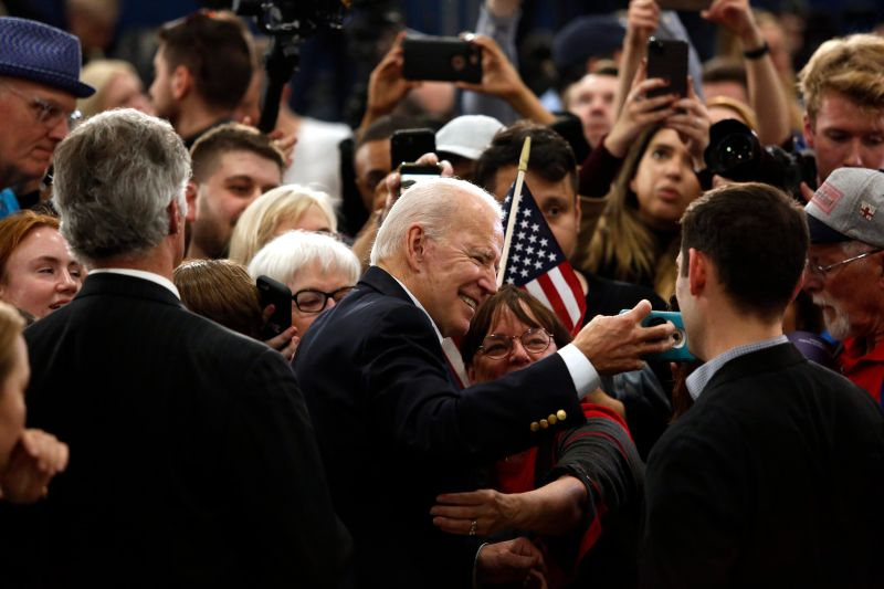 Joe Biden takes a selfie with an attendee during a campaign event