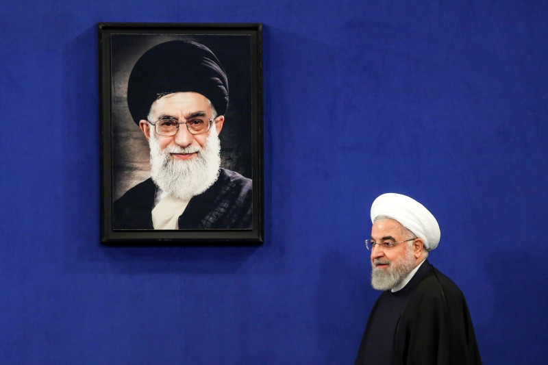 Iranian President Hassan Rouhani walks past a portrait of Supreme Leader Ayatollah Ali Khamenei in Tehran on Feb. 16.