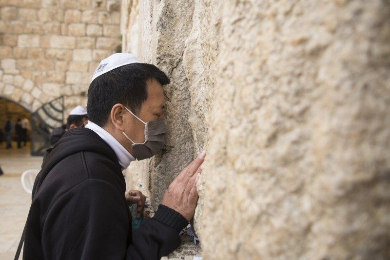 A man wearing a face mask prays during a mass prayer at the Western Wall