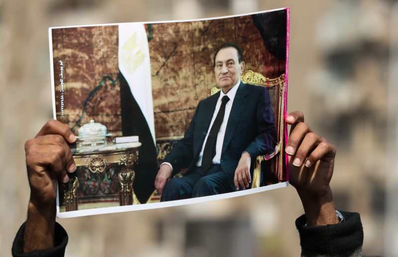 A supporter of Egypt's former President Hosni Mubarak lifts a picture of the late leader