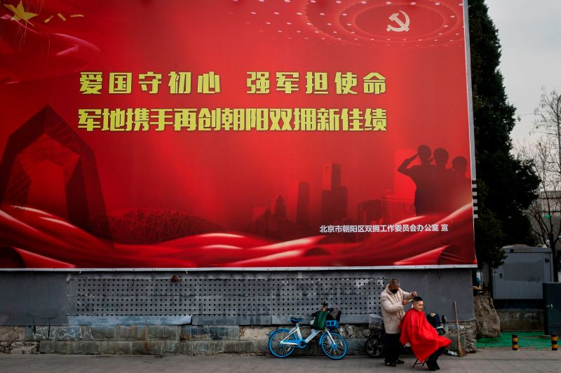 A street hairdresser cuts the hair of a customer as he wears a protective facemask as prevention for the spread of the COVID-19 coronavirus in-front of a propaganda poster on a street in Beijing on February 26, 2020.