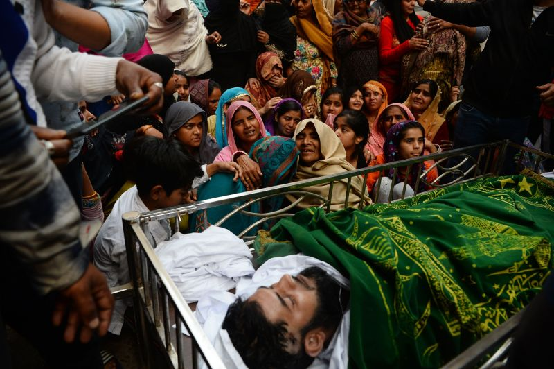 Mourners gather around the body of Mohammed Mudasir, who died in sectarian riots in New Delhi