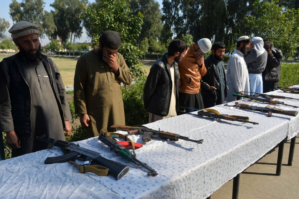 Former Afghan Taliban fighters stand next to weapons before handing them over as part of a government peace and reconciliation process at a ceremony in Jalalabad on March 1.