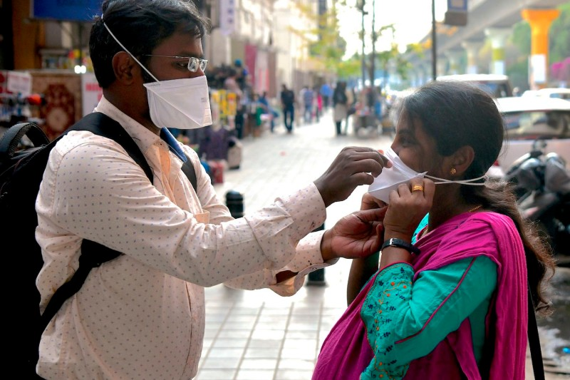 A man helps a woman wear a mask at the metro rail station in Bangalore on March 5, 2020.