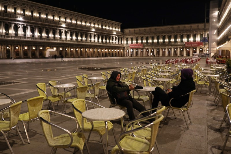 Two tourists sit in an empty San Marco Square on March 8, 2020 in Venice, Italy.