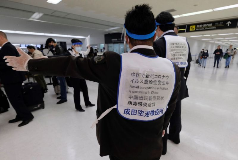 Officers assist passengers arriving at a quarantine station at Narita airport on March 9. Japanese Prime Minister Shinzo Abe announced on March 5 that foreign arrivals who have recently been in China or South Korea would be required to spend 14 days in quarantine.