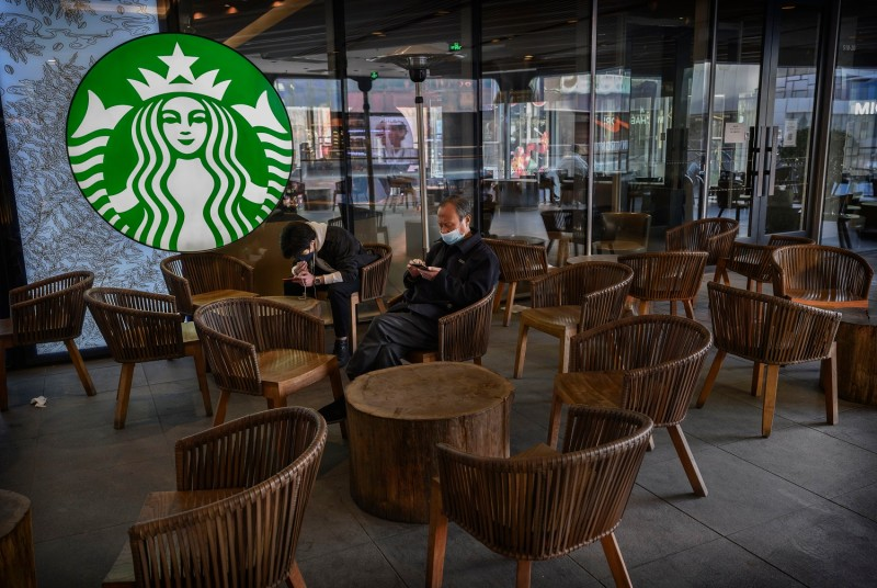 Two men wear protective masks as they sit in a nearly empty Starbucks in Sanlitun, Beijing, on March 10.