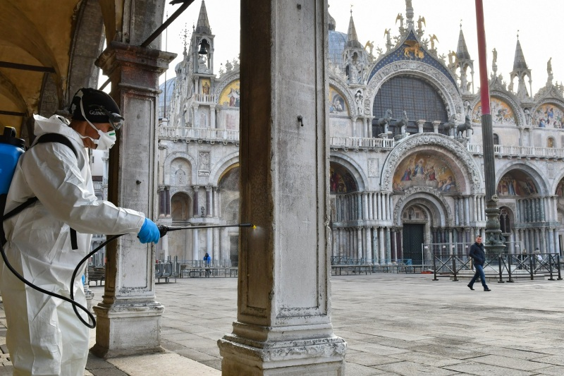 A municipal employee sprays disinfectant in St. Mark's Square in Venice, Italy