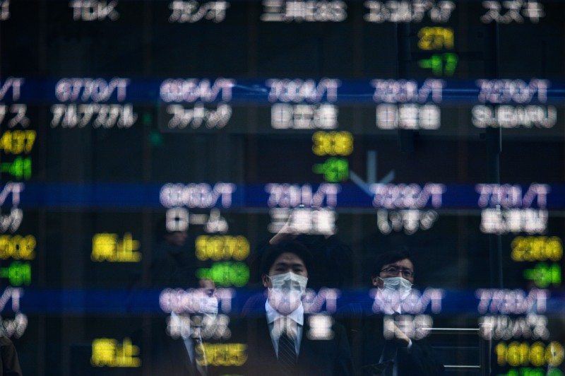 Pedestrians wearing face masks walk toward an electric board showing stocks' share price