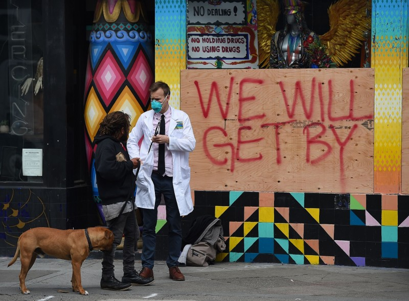 A doctor speaks with homeless people about the coronavirus