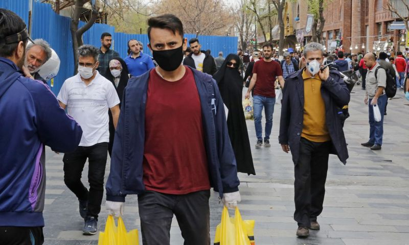 Iranians, some wearing protective masks