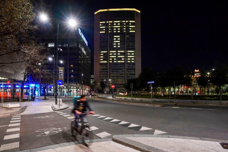 A picture taken on March 19, 2020 shows office lights of the Lombardy region headquarters in Milan, reading the Italian words 'State a Casa' (Stay home) during the country's lockdown aimed at stopping the spread of the new coronavirus pandemic.