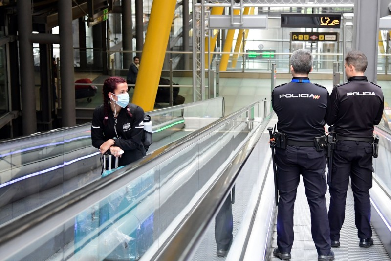 A passenger wearing a face mask as a protective measure looks at two police officers  at the Madrid-Barajas Adolfo Suarez Airport in Barajas on March 20, 2020.