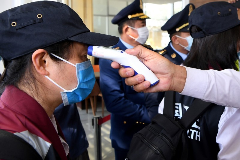 A quarantine official checks the temperature of a Chinese medical expert in Cambodia