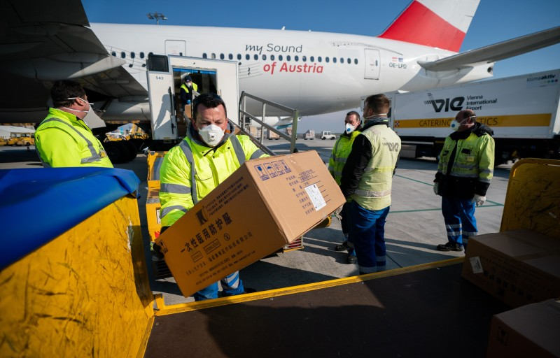 Workers at unload protective gear bound for Italy from an Austrian Airlines flight from China, at Vienna Airport on March 23, 2020.