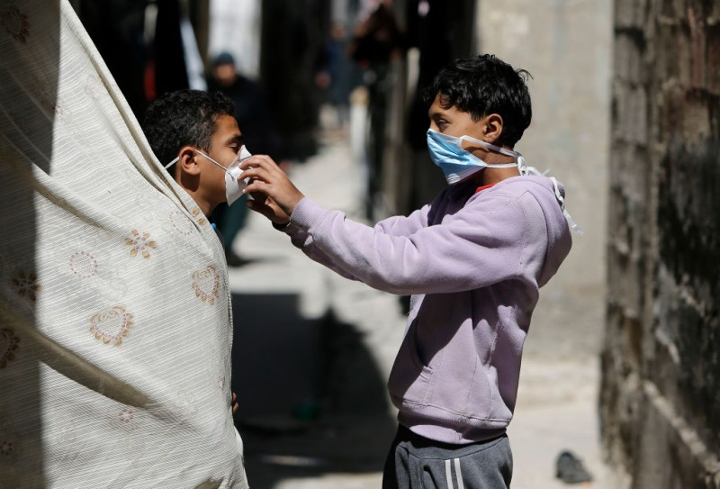 Palestinian children play with face masks