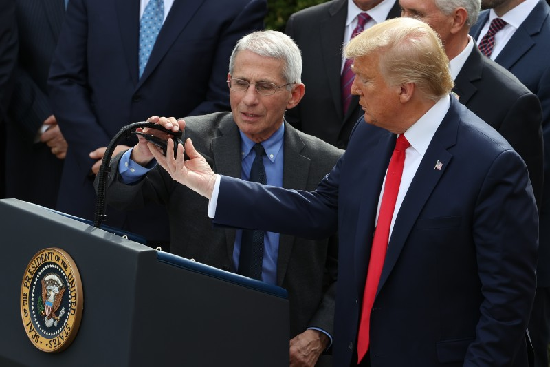 U.S. President Donald Trump adjusts the microphone for National Institute Of Allergy And Infectious Diseases Director Anthony Fauci