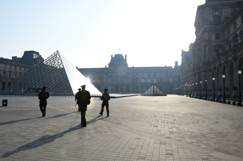 A military patrol walks past the empty Louvre Pyramid in Paris on March 28. The country has introduced fines for people caught violating its nationwide lockdown measures intended to stop the spread of COVID-19.