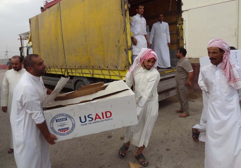Iraqi men unload USAID supplies north of Baghdad.