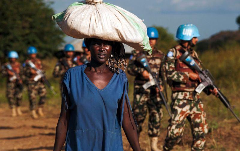 A woman carries goods near U.N. peacekeepers in South Sudan.