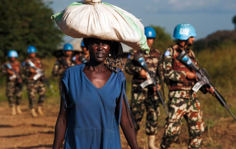 A woman carries goods near U.N. peacekeepers in South Sudan.