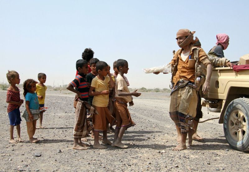 Pro-government fighters give food to children in Yemen.