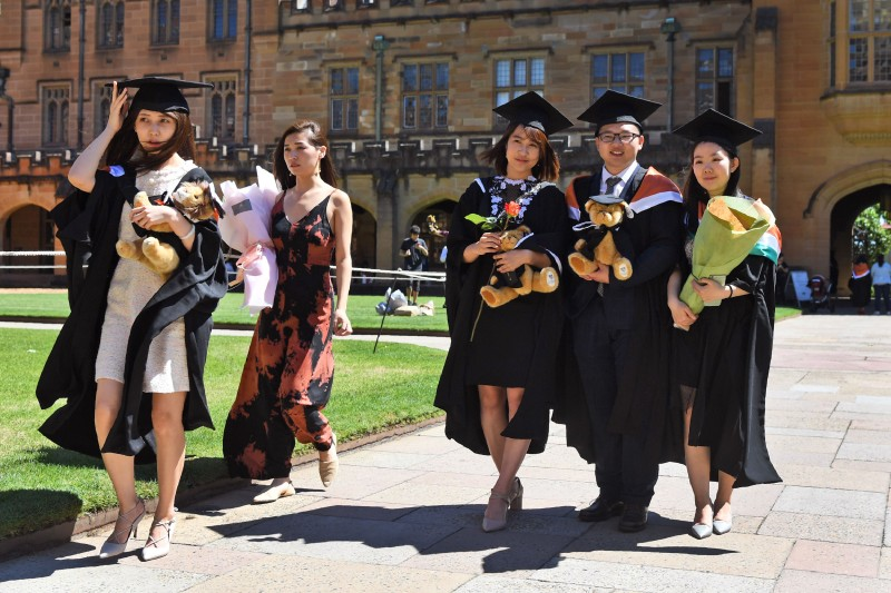 Chinese students pose for family photos after graduating from Sydney University on Oct. 12, 2017.