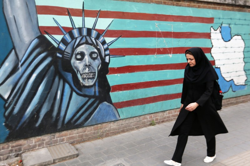 An Iranian woman walks past an anti-American mural on the wall of the former U.S. embassy in Tehran on May 8, 2018.