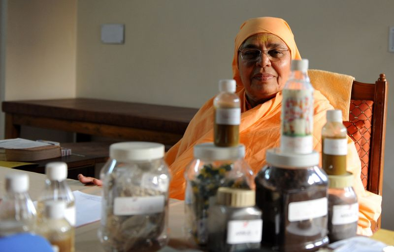 Shree Maa Anantanand sits behind medicine made from cow urine, which she uses to treat patients suffering kidney ailments and cancer at her hospital in Ahmedabad, India, on Feb. 27, 2010.