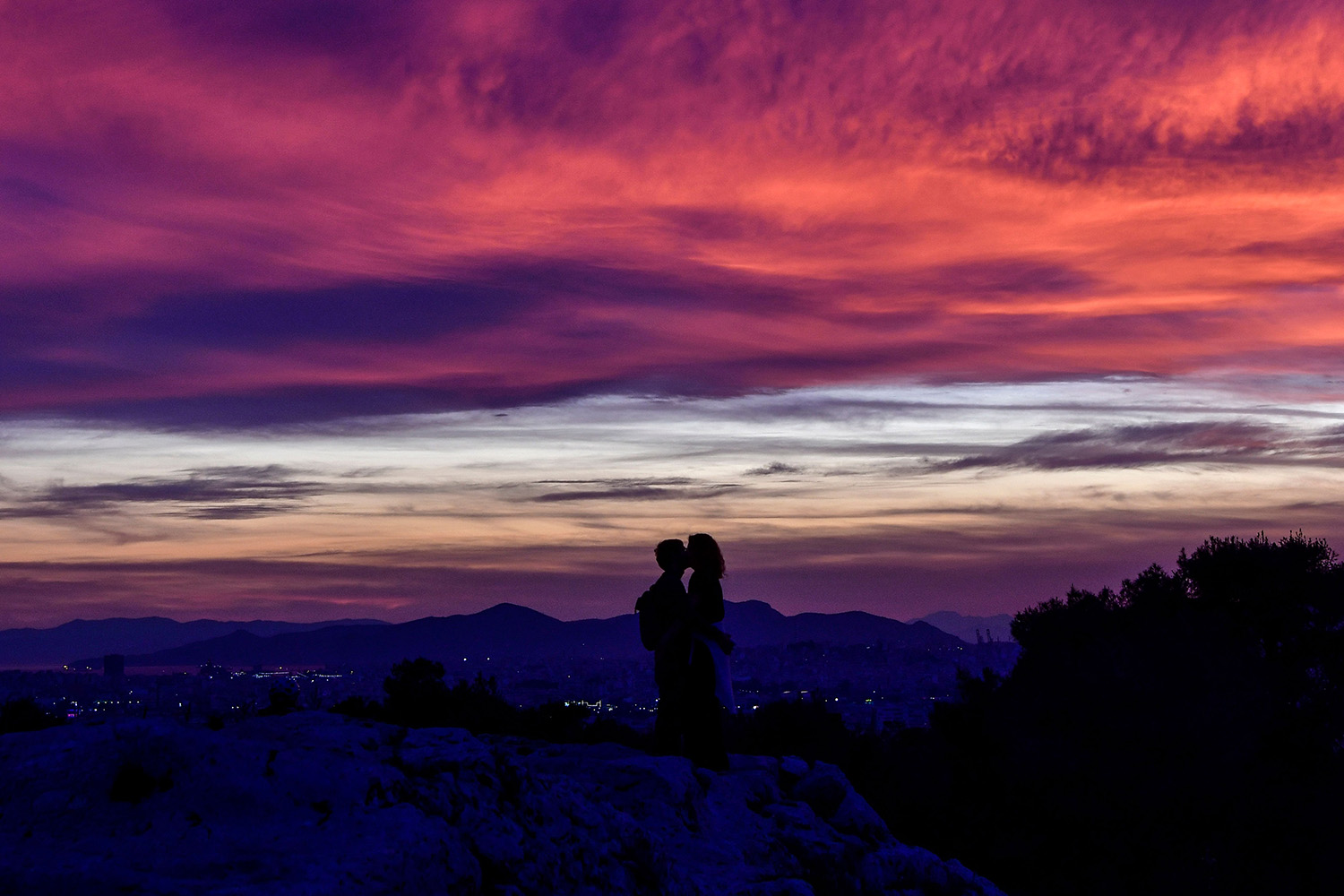 A couple kiss at sunset on a hill overlooking Athens, Greece, on March 14. LOUISA GOULIAMAKI/AFP via Getty Images