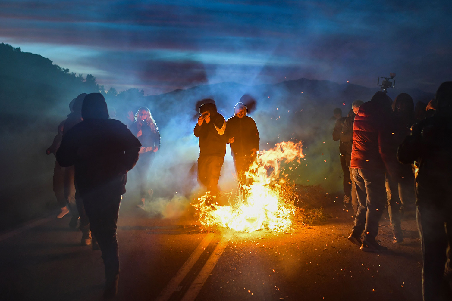 Demonstrators walk away from Greek anti-riot police as they protest against the construction of a new migrant camp near the town of Mantamados on the northeastern Aegean island of Lesbos on Feb. 25. ARIS MESSINIS/AFP via Getty Images