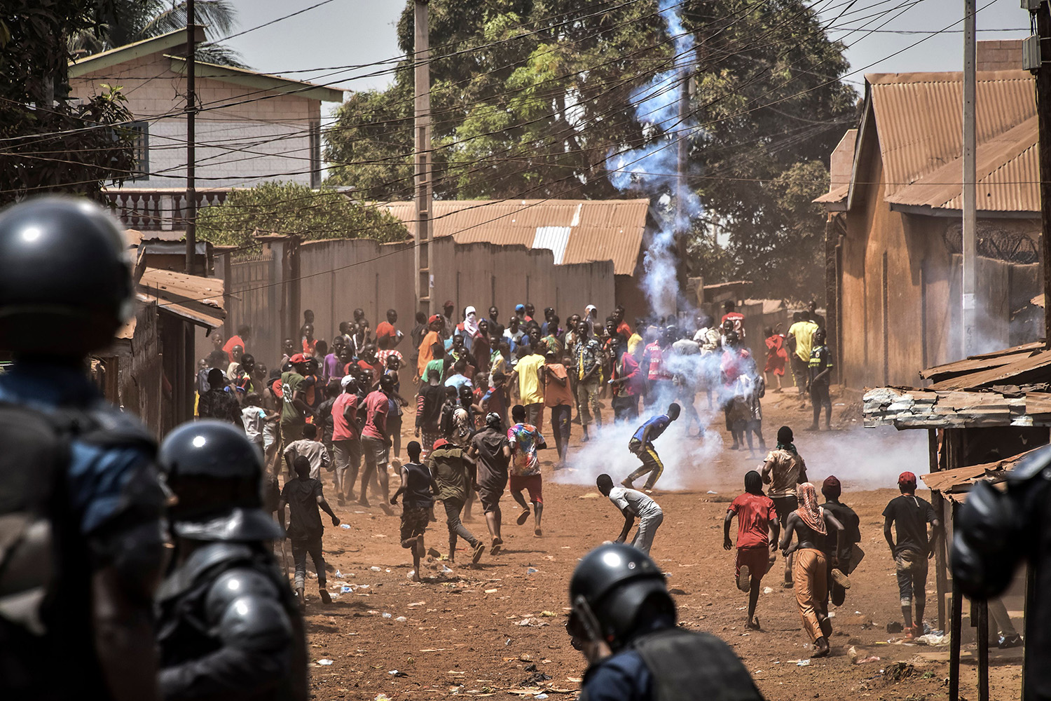 Protesters react as police throw rocks and fire tear gas in the opposition stronghold of Wanindara, a northern suburb of Conakry, Guinea, on Feb. 27. Guinea held a referendum on March 1 on whether to change the constitution to allow the president to run for a third term. CELLOU BINANI/AFP via Getty Images