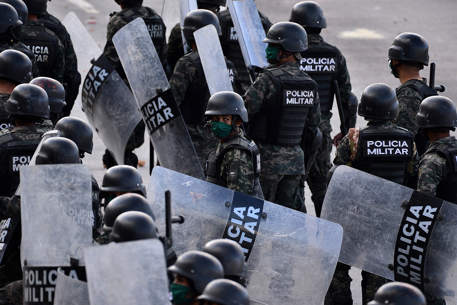 "Riot police walk toward drivers and workers blocking a street in Tegucigalpa, Honduras, on March 24 as they protest against ""an absolute curfew"" decreed by the government. ORLANDO SIERRA/AFP via Getty Images"