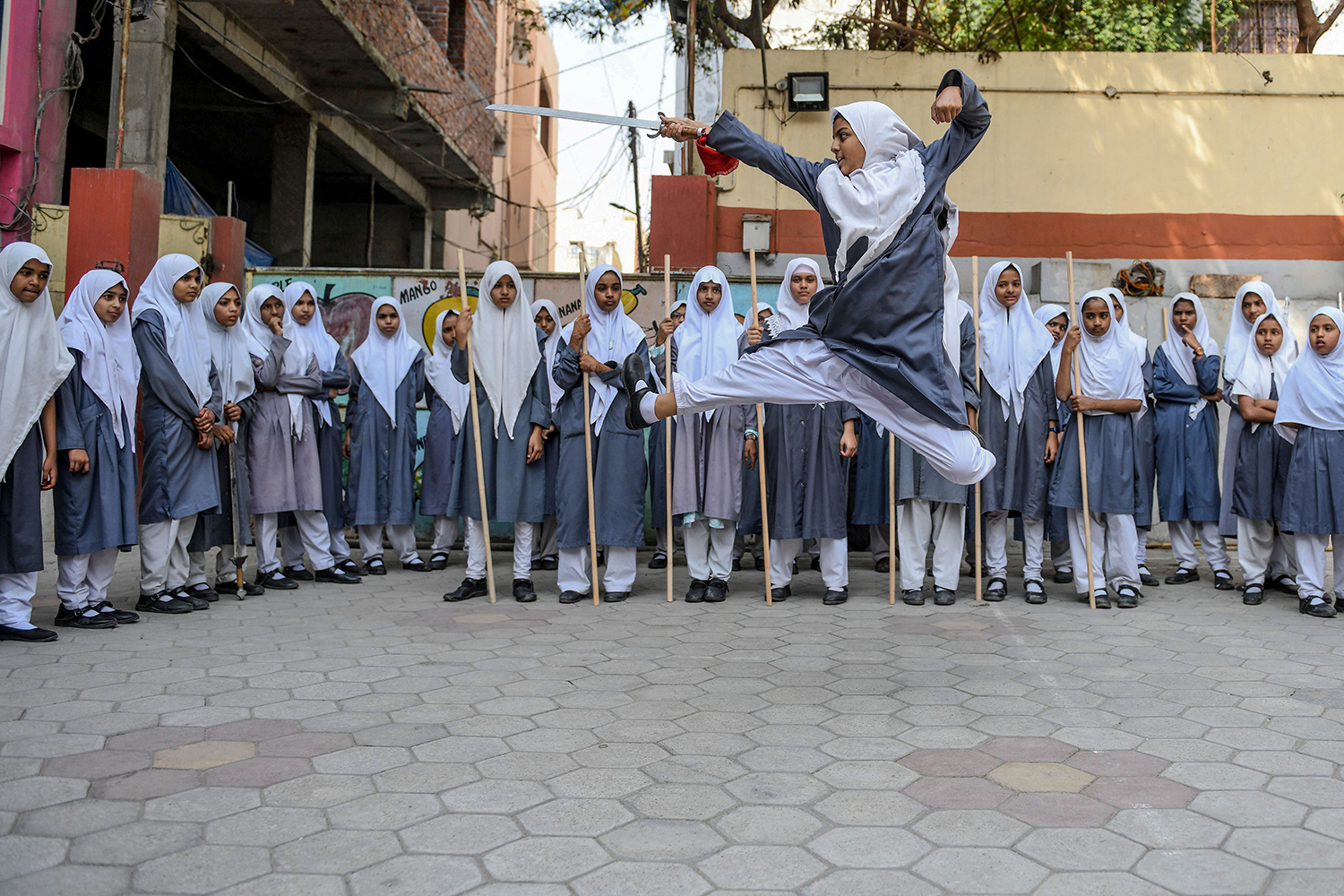 A girl practices Vovinam, a Vietnamese martial art of self-defense, with swords and sticks at St. Maaz High School in Hyderabad, India, on March 5. The school was preparing for an upcoming International Women's Day performance. NOAH SEELAM/AFP via Getty Images