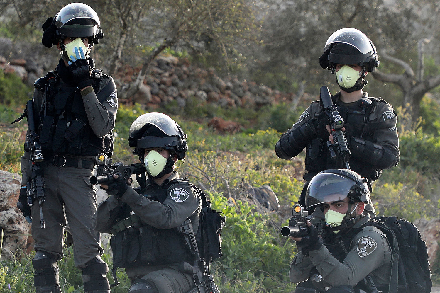 Israeli border guards wearing protective masks—seemingly to protect themselves from the coronavirus—aim their weapons at Palestinian youths during clashes in the occupied West Bank on March 11. A Palestinian teenager was reportedly killed when he was shot in the face. JAAFAR ASHTIYEH/AFP via Getty Images