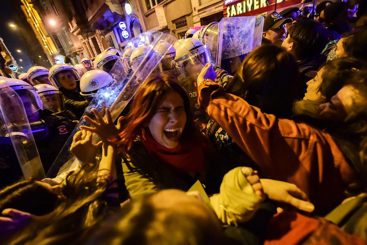 Turkish anti-riot police officers push back women during a rally marking International Women's Day in Istanbul on March 8. Istanbul police fired tear gas at thousands of women who took to the city's central avenue in defiance of a protest ban to demand greater rights and denounce violence. YASIN AKGUL/AFP via Getty Images