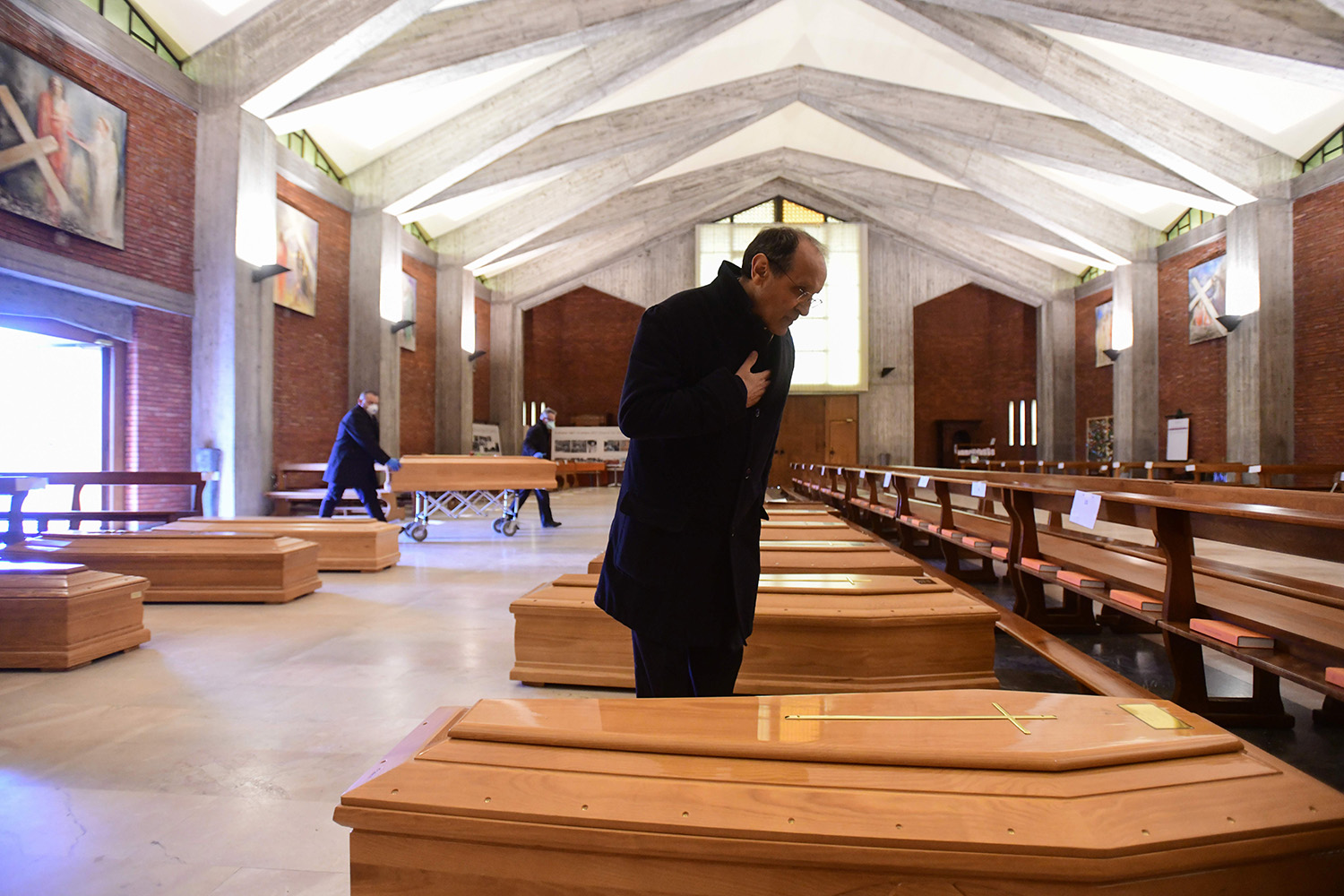 A parish priest prays over one of the coffins being stored in San Giuseppe's church in Seriate, a northern-Italian town, on March 26. PIERO CRUCIATTI/AFP via Getty Images