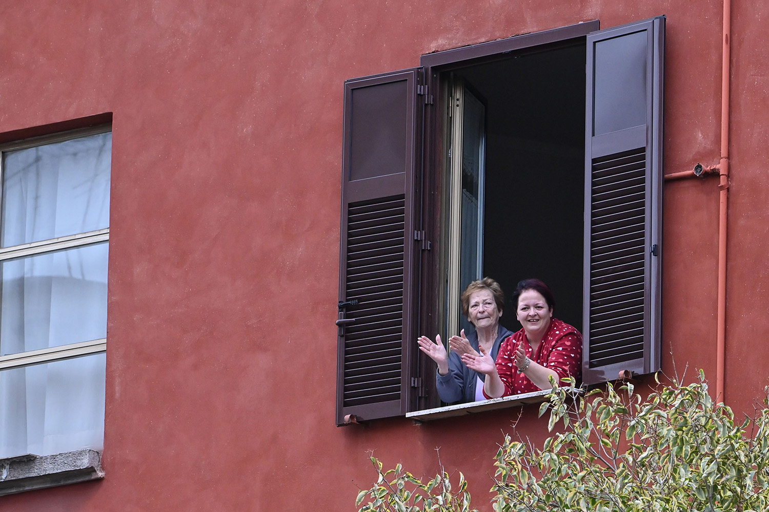 """Women clap their hands during a flash mob """"un applauso per l'Italia"""" (an applause for Italy) in Rome on March 14. People throughout Italy were encouraged to gather on balconies and at windows to sing, play, or listen to music to lift spirits and break the monotony of the coronavirus lockdown. ANDREAS SOLARO/AFP via Getty Images"""