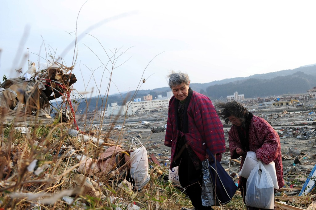 Residents walk past debris after an earthquake and tsunami struck Japan in 2011
