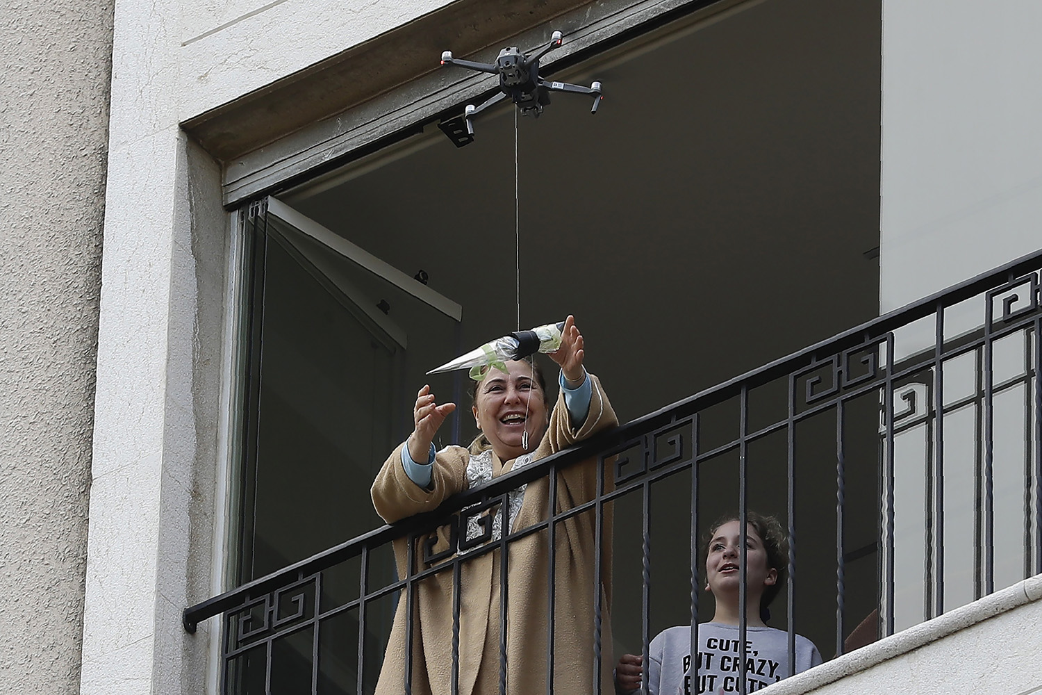 A woman standing on her balcony reaches out to catch a rose delivered to her via a drone on Mother's Day in the Lebanese coastal city of Jounieh, north of Beirut, on March 21. Three students came up with the service to celebrate the occasion without flouting social distancing restrictions. JOSEPH EID/AFP via Getty Images